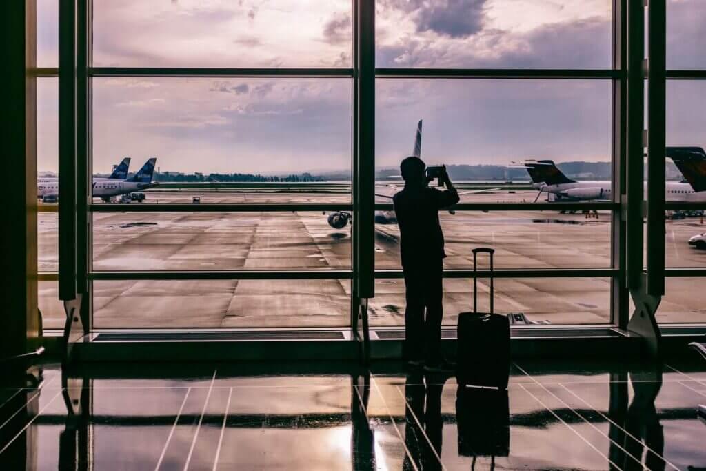 Hombre tomando foto en un aeropuerto. Hay importantes demoras para la obtención de visados