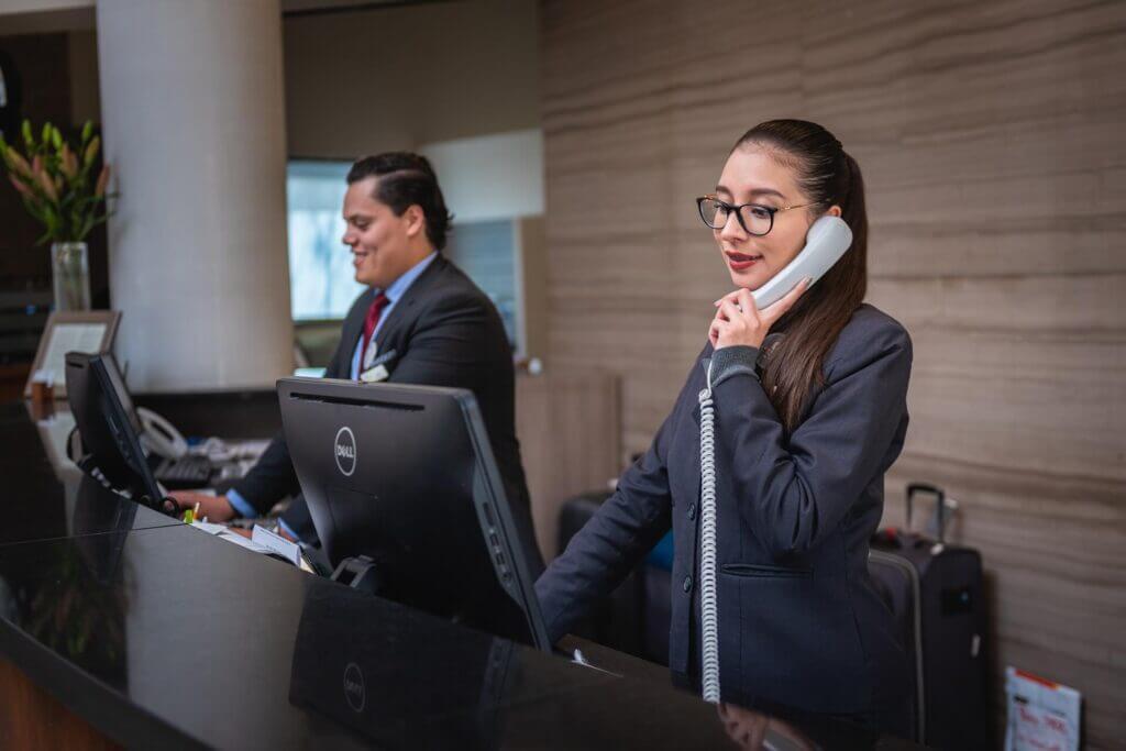 Dos recepcionistas trabajando en un hotel - El gobierno anunció un aumento del número de visas temporales para trabajar en Estados Unidos