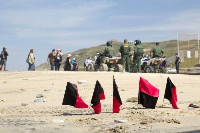 En la noticia se informa sobre el plan para acelerar los casos legales de las familias que llegan a la frontera México Estados Unidos. La imagen es una foto de oficiales de la patrulla fronteriza junto a personas migrantes.