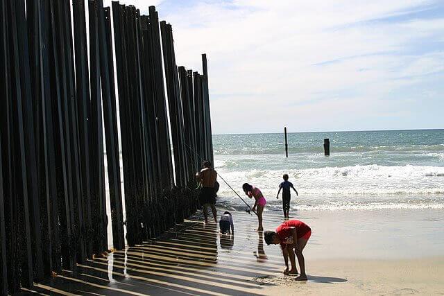 La nota es sobre el cierre de frontera México Estados Unidos. La imagen es de una familia junto al muro fronterizo.
