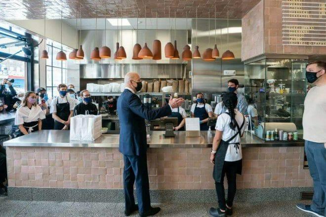Esta nota es sobre el apoyo de los líderes empresariales a la Reforma Migratoria de Biden. La imagen es del presidente Biden junto a trabajadores gastronómicos.