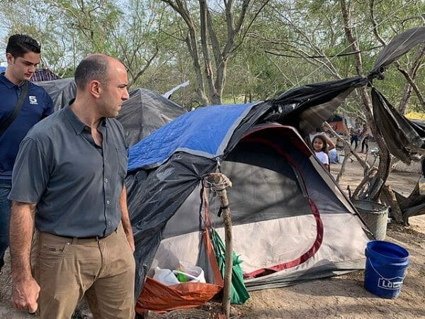 Nota sobre la posible reactivación del programa Remain in Mexico. La imagen es de un campamento en la frontera.